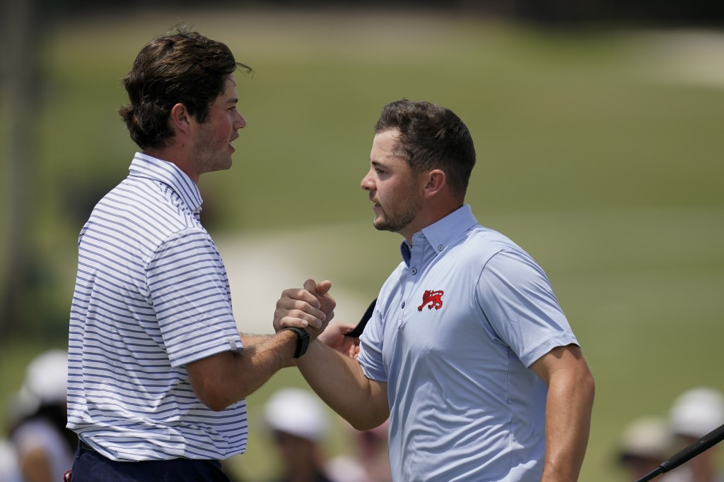Alex Fitzpatrick, right, of the Great Britain and Ireland team, congratulates Cole Hammer, of the USA team, on the 18th hole in the foursome matches d...