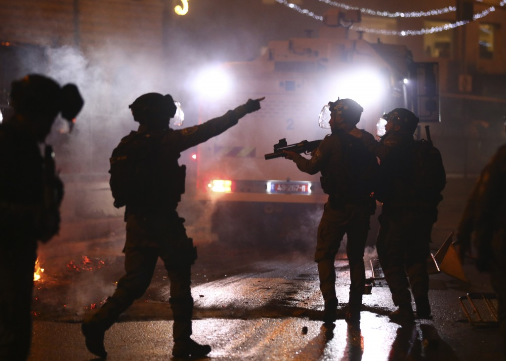 Israeli police officers fire stun grenades towards Palestinian demonstrators during clashes at Damascus Gate just outside Jerusalem's Old City, Saturd...