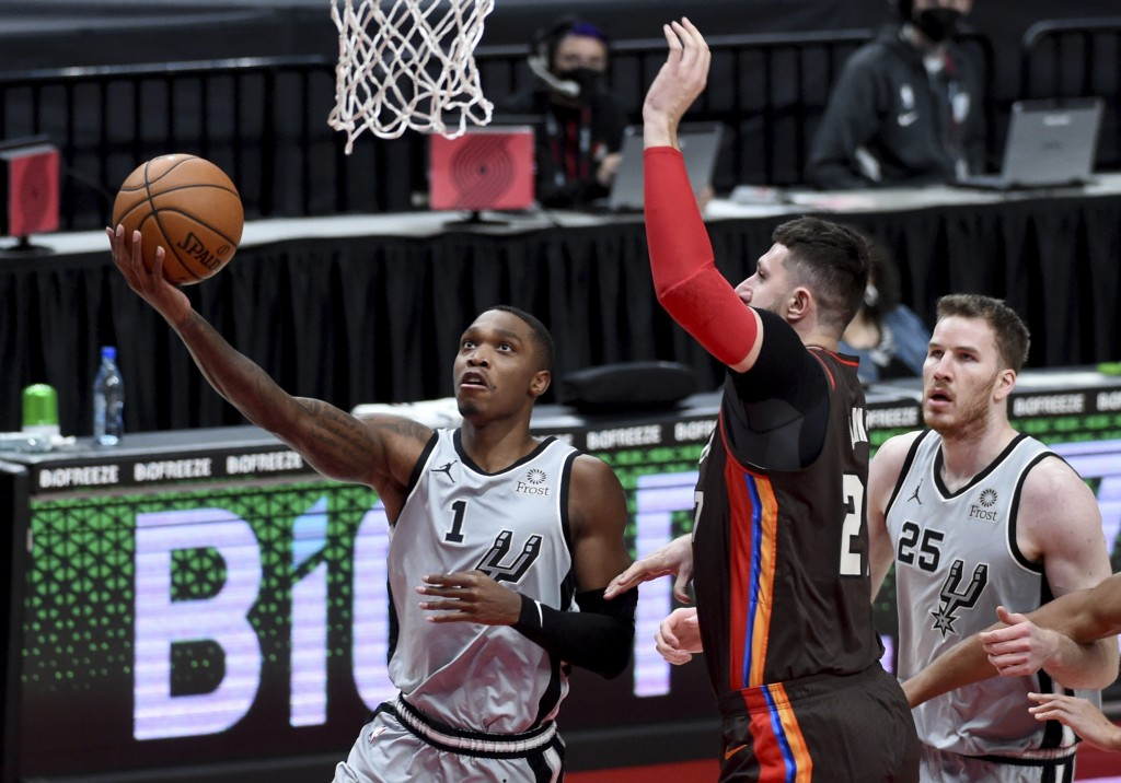 San Antonio Spurs guard Lonnie Walker IV, left, drives to the basket on Portland Trail Blazers center Jusuf Nurkic during the first half of an NBA bas...