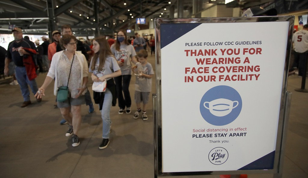People make their way into Truist Park as they pass signage thanking fans for wearing a face mask per CDC guidelines prior to the baseball game betwee...