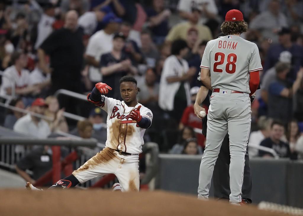 Atlanta Braves' Ozzie Albies, left, celebrates beside Philadelphia Phillies third baseman Alec Bohm (28) after hitting a triple in the fourth inning o...
