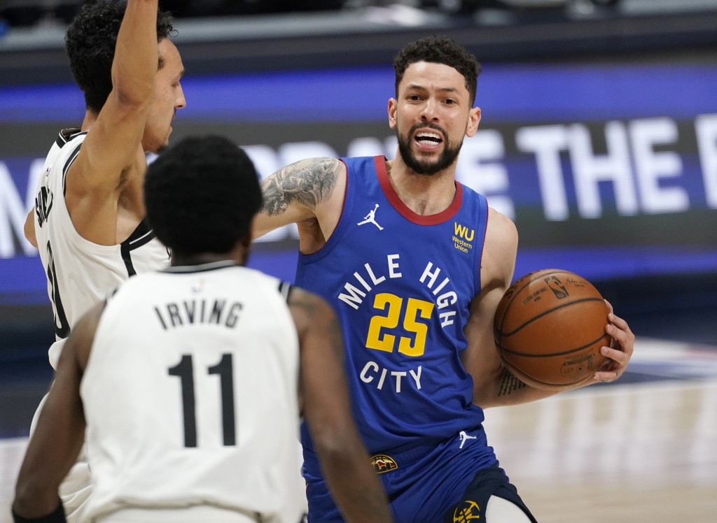 Denver Nuggets guard Austin Rivers, right, drives as Brooklyn Nets guards Landry Shamet, back left, and Kyrie Irving defend during the first half of a...