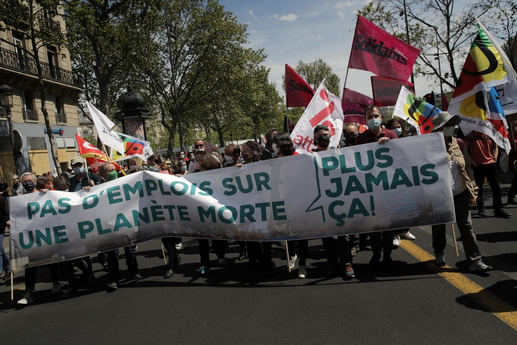 Protester hold a banner reading «No job on a dead planet» during a rally against the climate change in Paris, Sunday, May 9, 2021. Thousands of French...