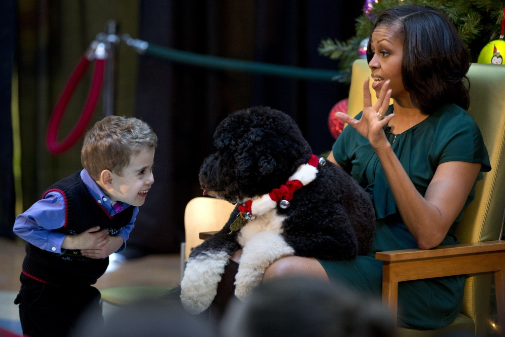 FILE - In this Dec. 14, 2012, file photo A.J. Murray, left, peeks in close at first dog Bo, as first lady Michelle Obama, answers questions from child...