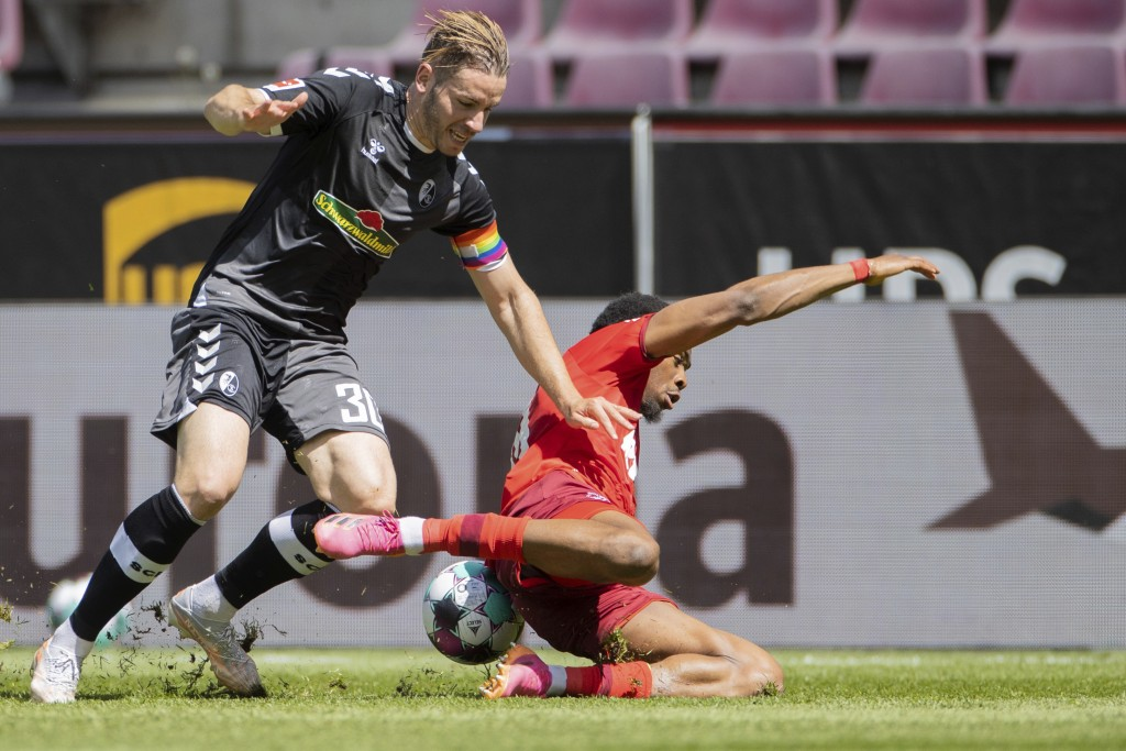 Cologne's Kingsley Ehizibue, right, and Freiburg's Christian Guenter, left, challenge for the ball during the German Bundesliga soccer match between 1...