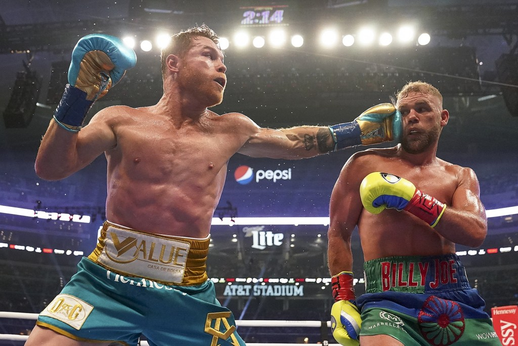 Canelo Alvarez, left, connects against Billy Joe Saunders during a unified super middleweight world championship boxing match, Saturday, May 8, 2021, ...
