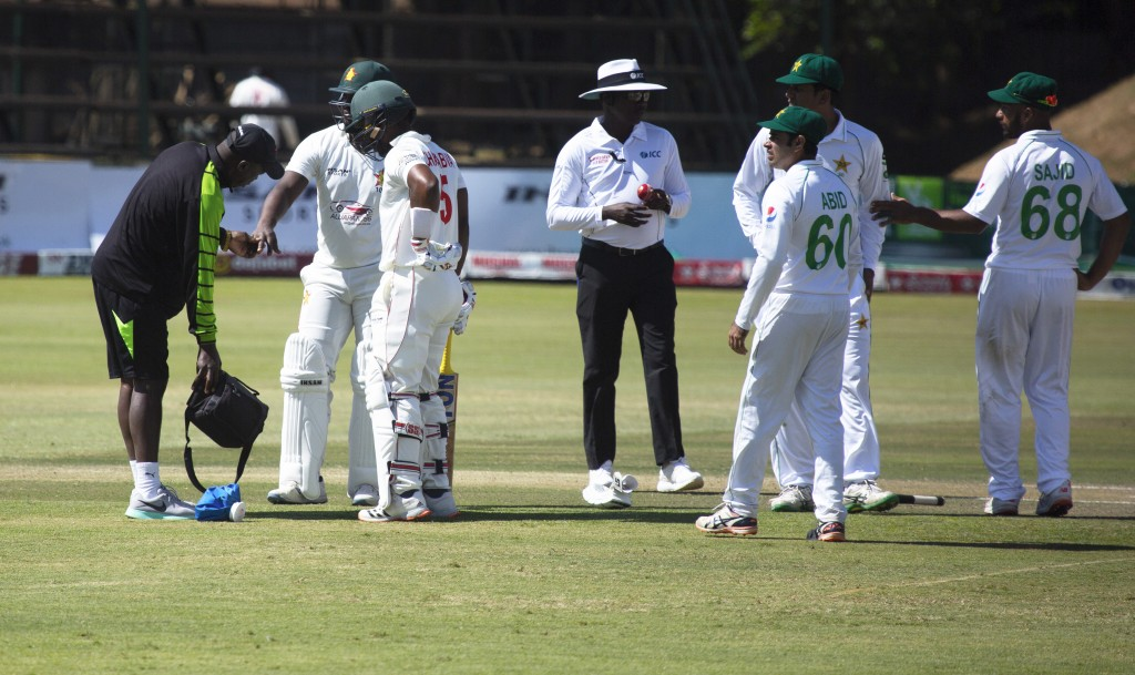 A medic attends to Zimbabwe batsman Regis Chakabva, left, after he was injured his finger,  during the second test cricket match between Zimbabwe and ...