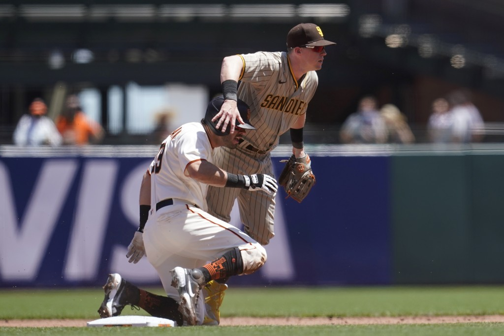 San Diego Padres second baseman Jake Cronenworth, top, looks toward first base after forcing San Francisco Giants' Mike Tauchman, bottom, out at secon...