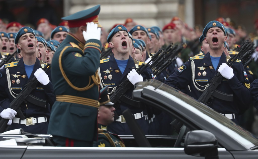 Russian Defense Minister Sergei Shoigu salutes to his soldiers as he is driven along Red Square in the Aurus Senat car during the Victory Day military...