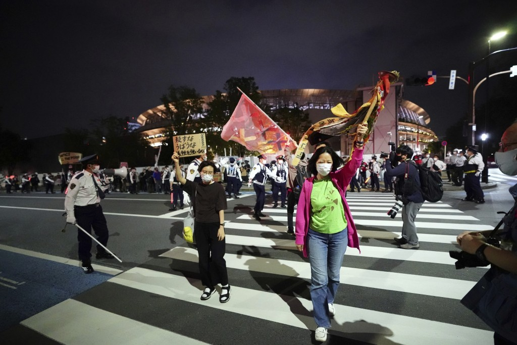 People who are against the Tokyo 2020 Olympics set to open in July, march around Tokyo's National Stadium, back, during an anti-Olympics demonstration...