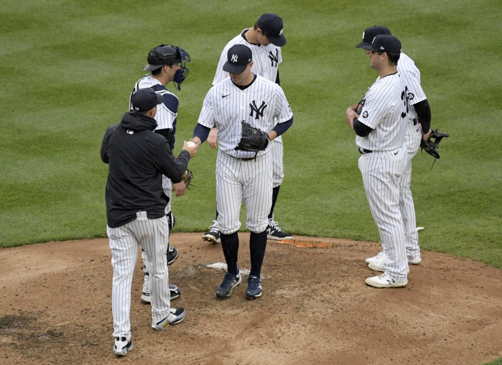 New York Yankees pitcher Corey Kluber hands the ball to manager Aaron Boone as he leaves the baseball game during the sixth inning against the Washing...