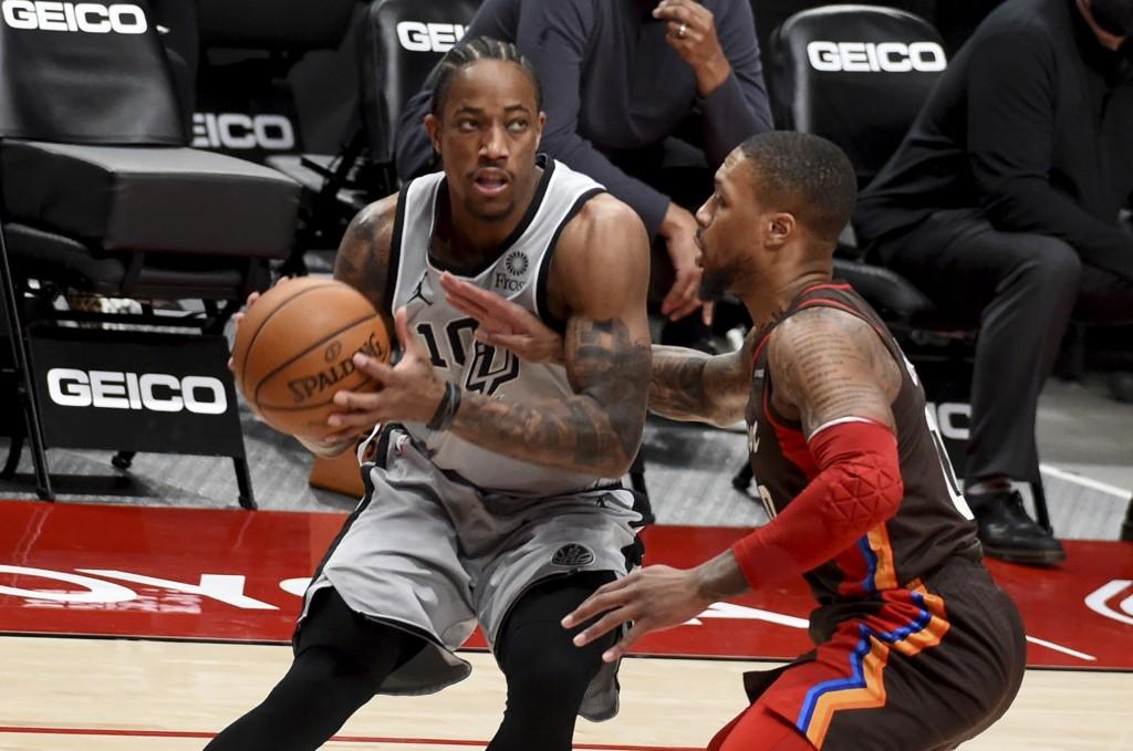 San Antonio Spurs forward DeMar DeRozan, left, is defended by Portland Trail Blazers guard Damian Lillard during the first half of an NBA basketball g...