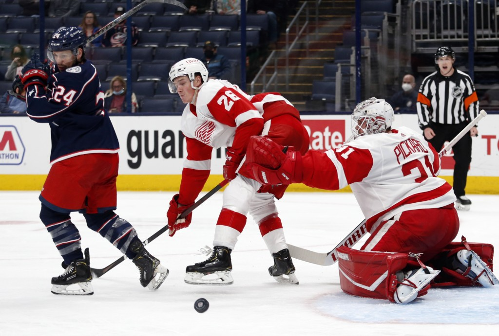 Detroit Red Wings goalie Calvin Pickard, right, makes a stop behind Columbus Blue Jackets forward Nathan Gerbe, left, and Red Wings defenseman Gustav ...