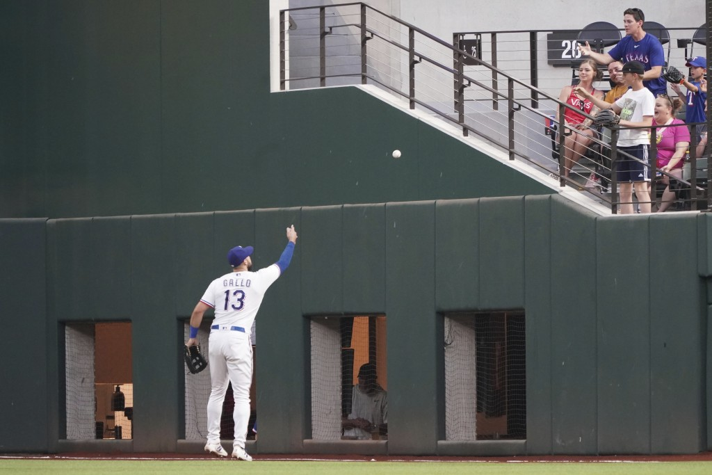 Texas Rangers right fielder Joey Gallo tosses a ball to a fan after catching it in the fifth inning of a baseball game against the Seattle Mariners, S...
