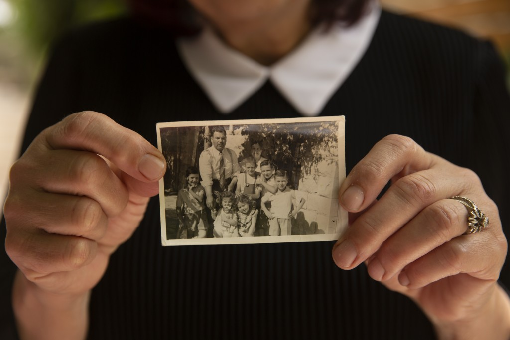 Samira Dajani holds a photo of her family in 1956 after they moved into their home in the Sheikh Jarrah neighborhood of east Jerusalem, Sunday, May 9,...
