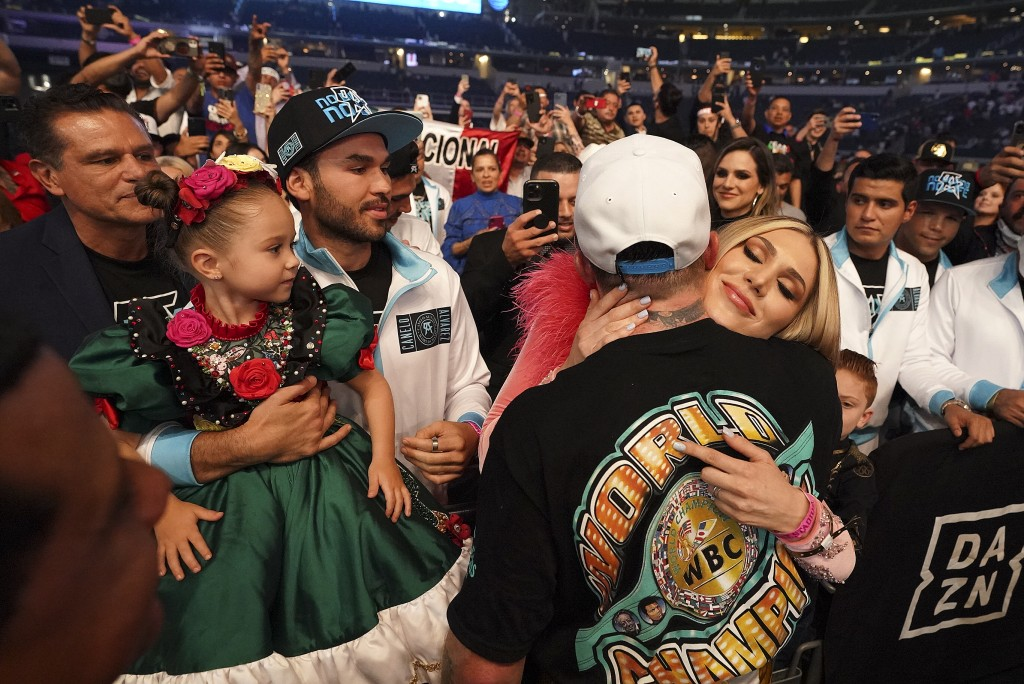 Canelo Alvarez hugs his girlfriend, Fernanda Gomez as their daughter, Maria, left, looks on, after defeating Billy Joe Saunders in a unified super mid...