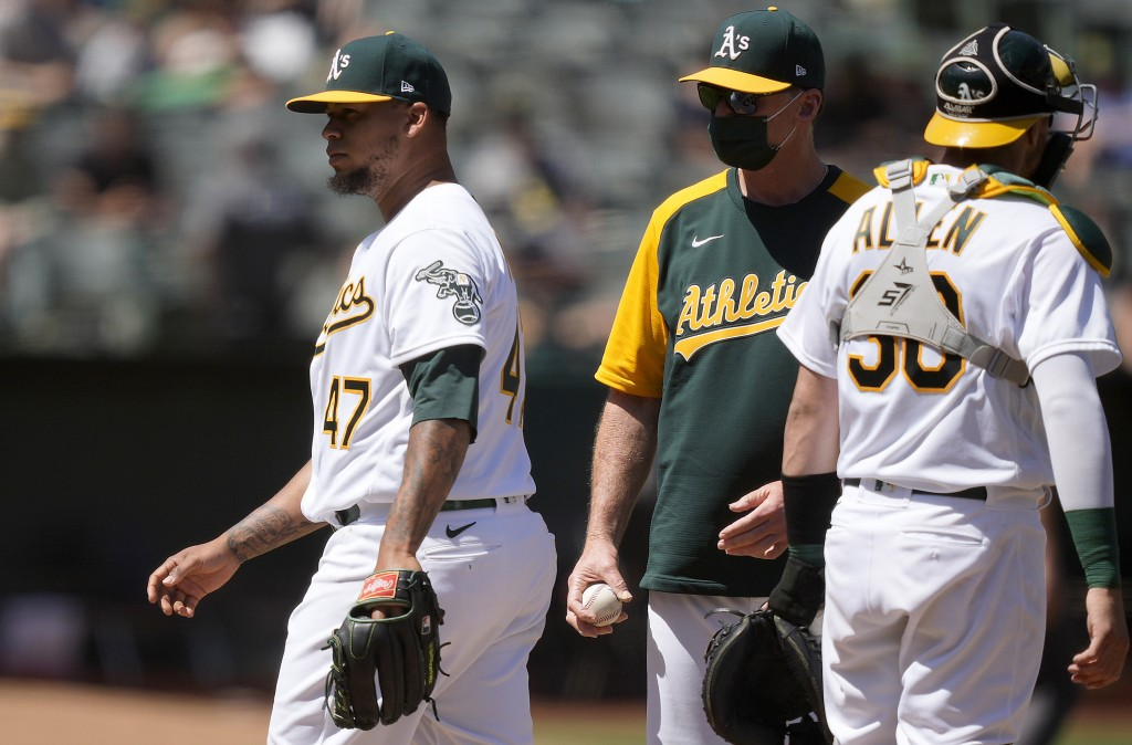 Oakland Athletics starting pitcher Frankie Montas (47) is taken out by Bob Melvin, center, during the sixth inning of a baseball game against the Tamp...