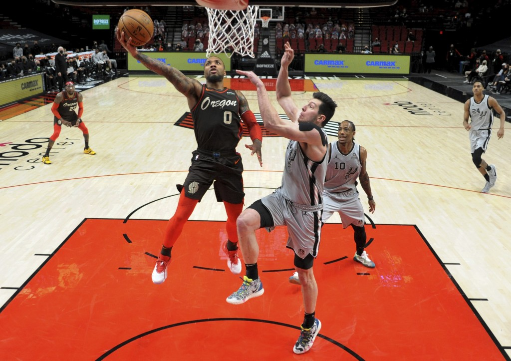 Portland Trail Blazers guard Damian Lillard, left drives to the basket on San Antonio Spurs forward Drew Eubanks, right, during the second half of an ...