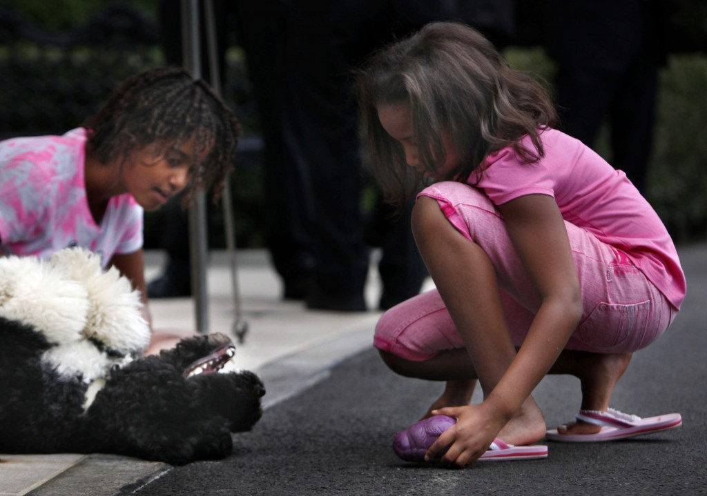FILE - In this Sept. 15, 2009, file photo Malia Obama, left, and Sasha Obama play with family dog Bo as they wait for President Barack Obama to arrive...