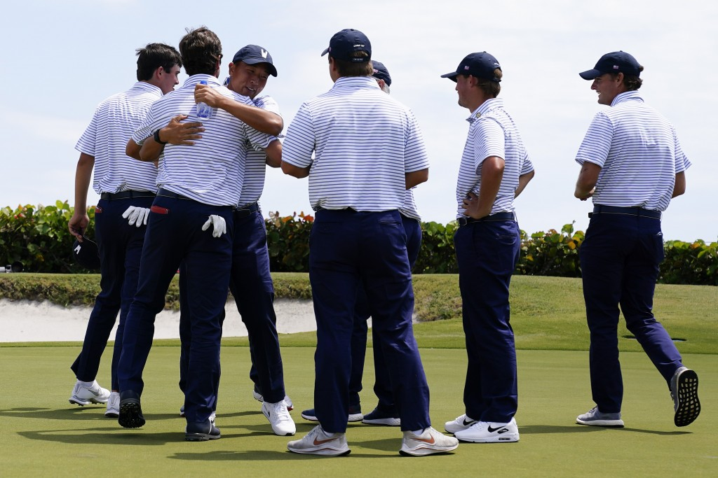 Members of the USA team celebrate after Cole Hammer and Davis Thompson won their match against Great Britain and Ireland team on the 18th hole in the ...