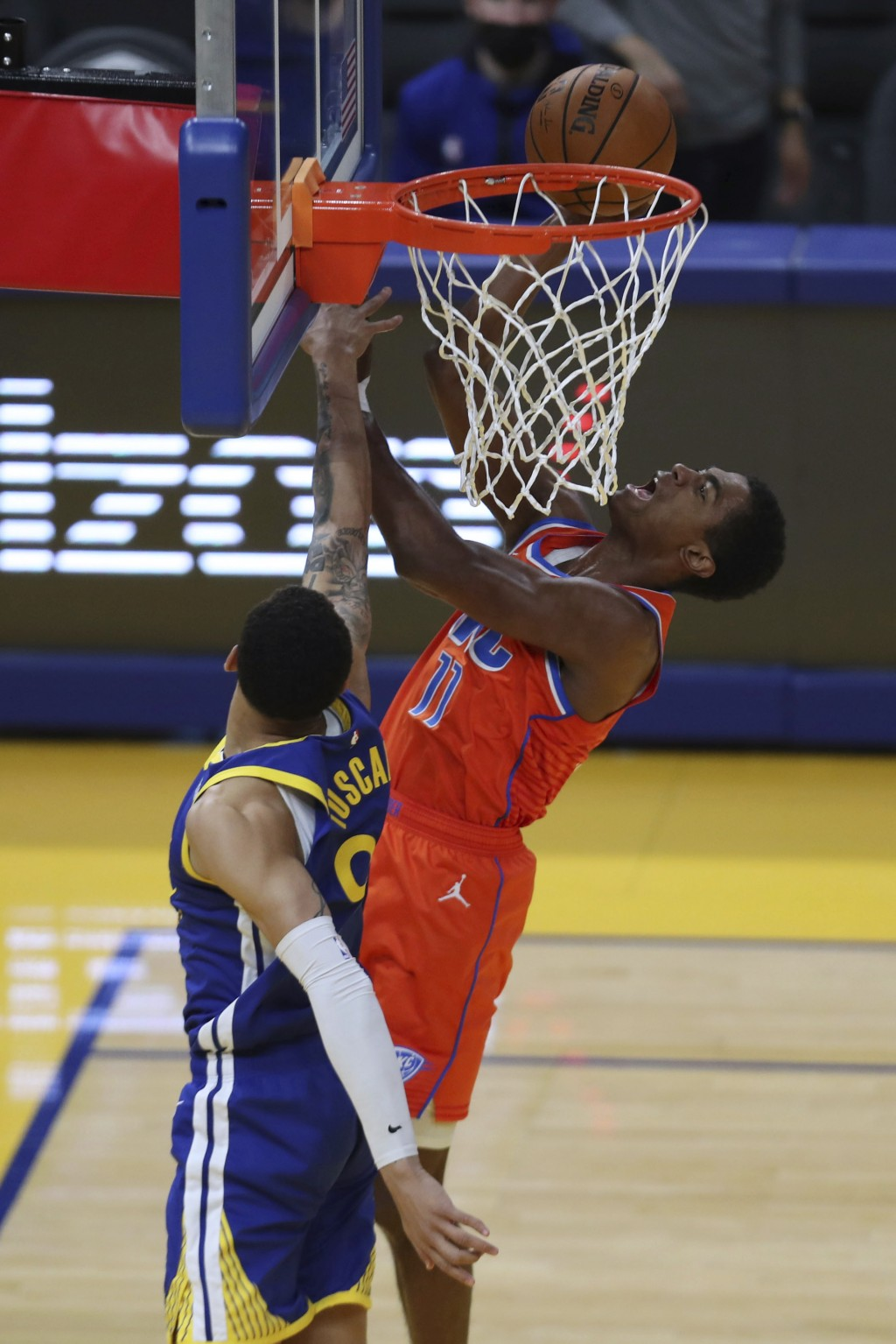 Oklahoma City Thunder's Théo Maledon, right, shoots against Golden State Warriors' Juan Toscano-Anderson during the second half of an NBA basketball g...