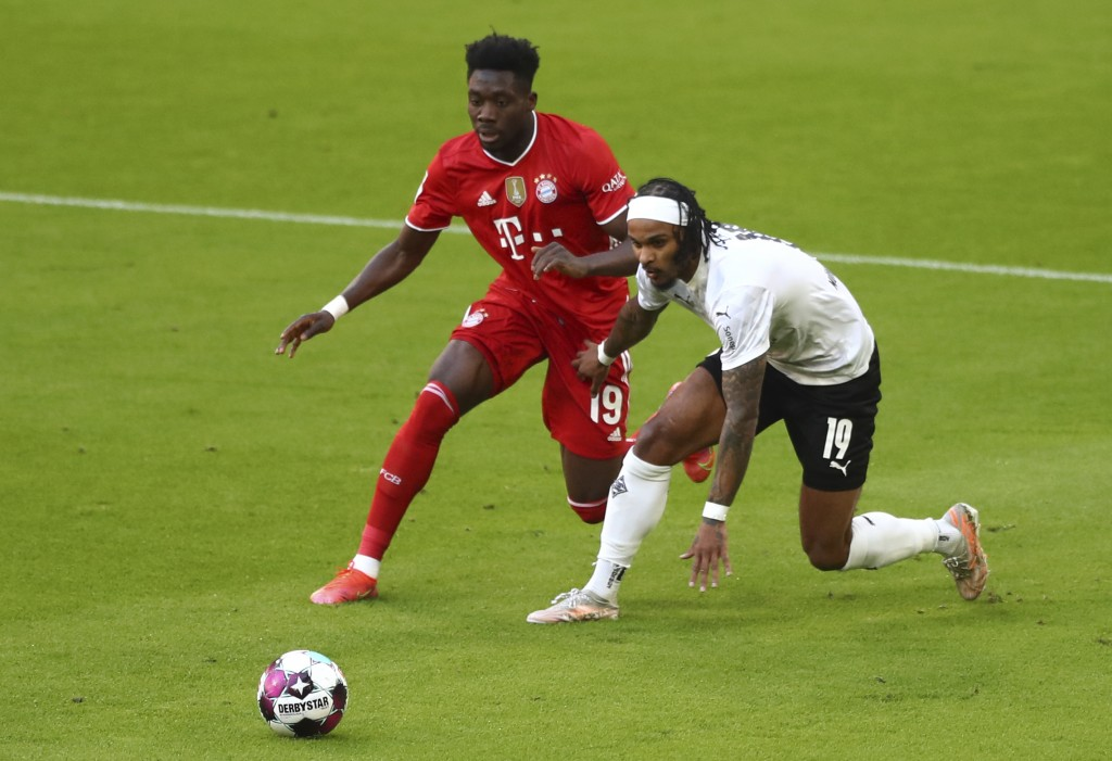 Bayern's Alphonso Davies, left, and Moenchengladbach's Valentino Lazaro challenge for the ball during the German Bundesliga soccer match between Bayer...