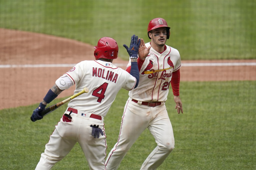 St. Louis Cardinals' Nolan Arenado, right, is congratulated by teammate Yadier Molina (4) after scoring during the fifth inning of a baseball game aga...