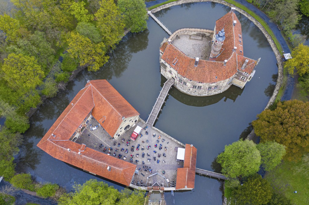 In this aerial view taken with a drone, around 100 spectators are seated during a concert as part of the Coesfeld model region at Burg Vischering, in ...