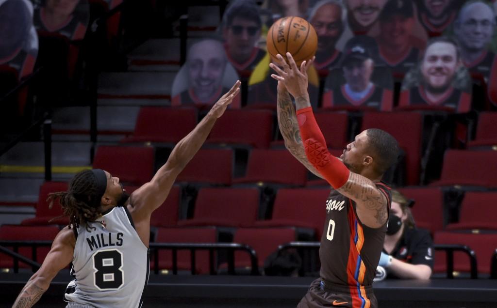 Portland Trail Blazers guard Damian Lillard shoots over San Antonio Spurs guard Patty Mills during the first half of an NBA basketball game in Portlan...