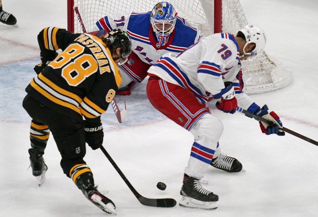 New York Rangers goaltender Keith Kinkaid, center, eyes the puck on a shot by Boston Bruins right wing David Pastrnak (88) during the first period of ...