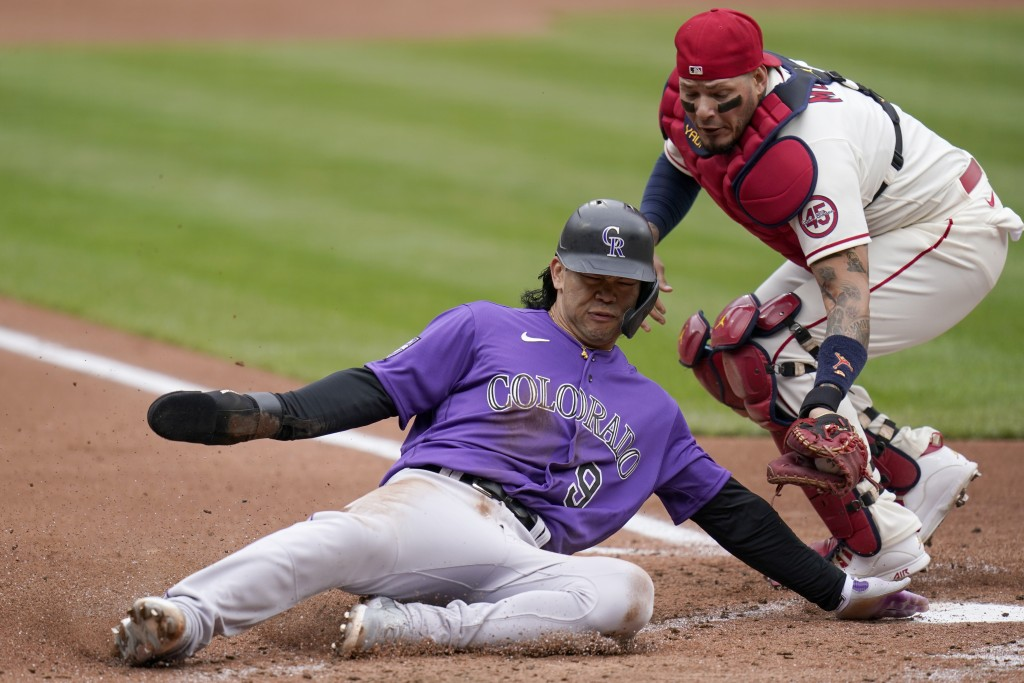 Colorado Rockies' Connor Joe (9) slides after being tagged out at home by St. Louis Cardinals catcher Yadier Molina during the second inning of a base...