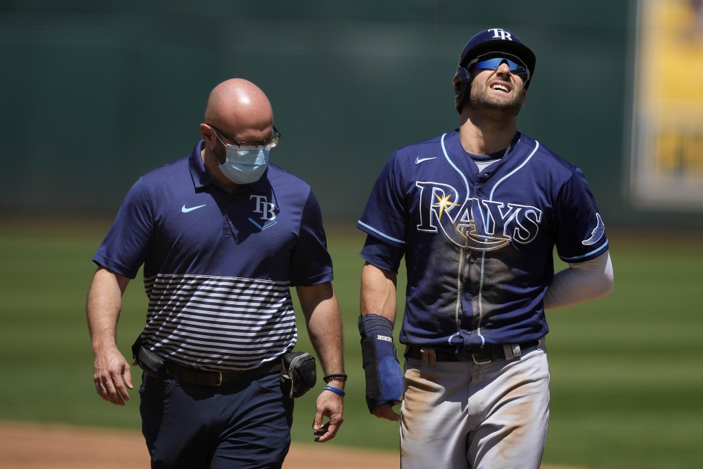 Tampa Bay Rays' Kevin Kiermaier, right, walks with a trainer back to the dugout after suffering an injury while stealing second base during the second...