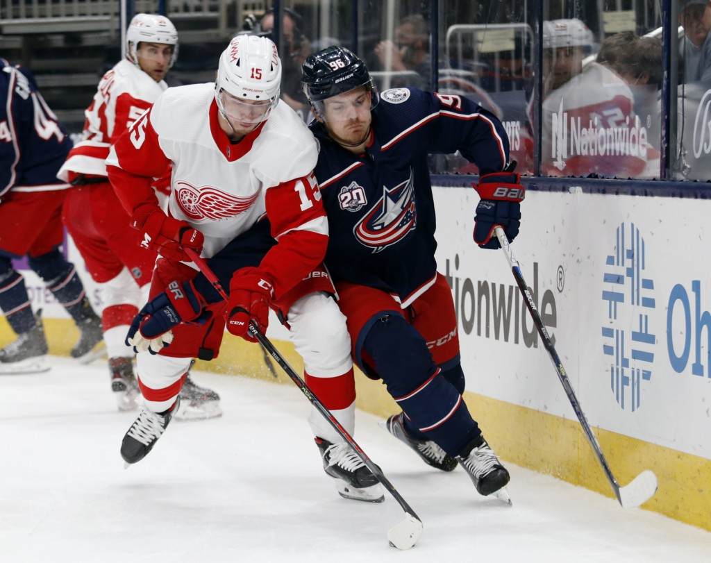 Detroit Red Wings forward Jakub Vrana, left, controls the puck in front of Columbus Blue Jackets forward Jack Roslovic during the first period of an N...