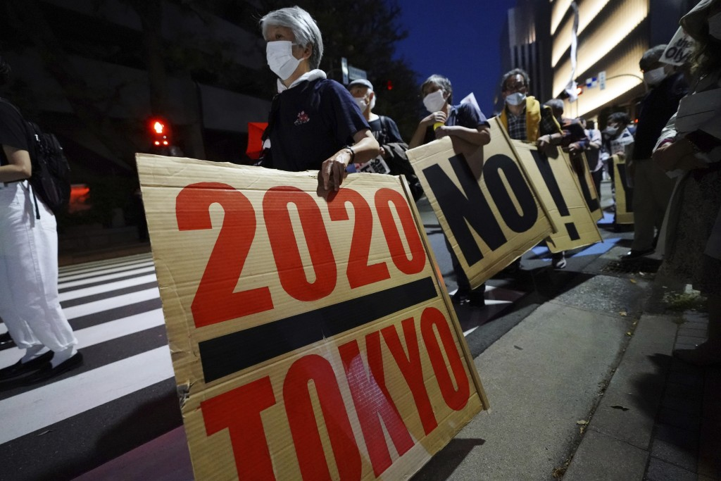 People who are against the Tokyo 2020 Olympics set to open in July, march around Tokyo's National Stadium during an anti-Olympics demonstration Sunday...