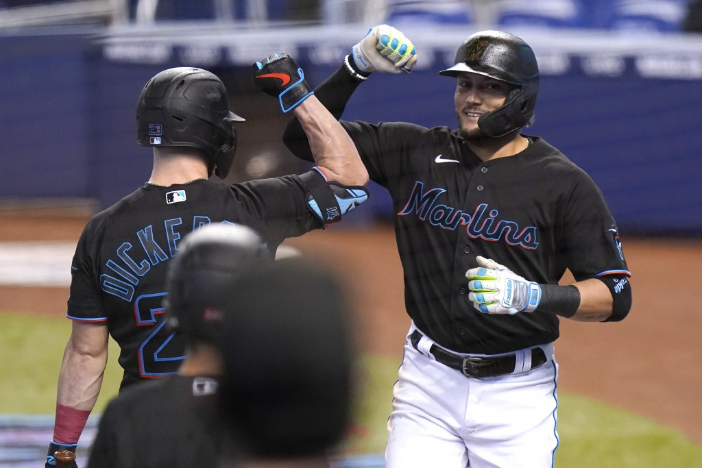 Miami Marlins' Miguel Rojas, right, is met by Corey Dickerson after hitting a solo home run during the first inning of a baseball game against the Mil...