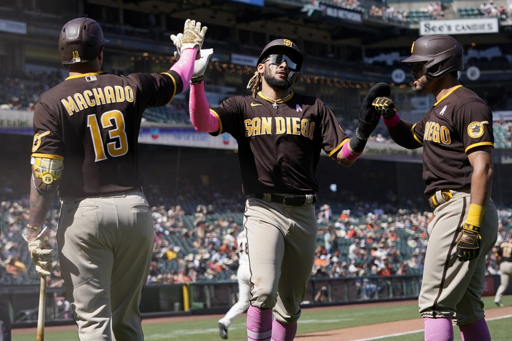 San Diego Padres' Fernando Tatis Jr., middle, and Tommy Pham, right, are congratulated by Manny Machado (13) after both scored on a two-run triple hit...