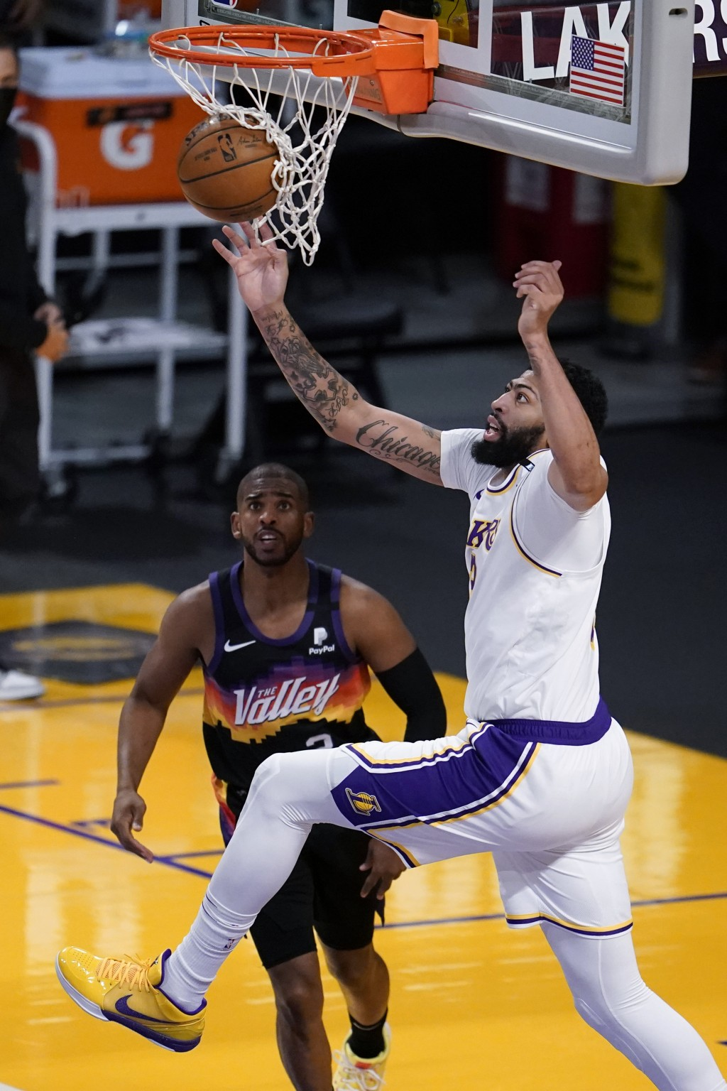 Los Angeles Lakers forward Anthony Davis, right, reaches for a rebound over Phoenix Suns guard Chris Paul during the first half of an NBA basketball g...