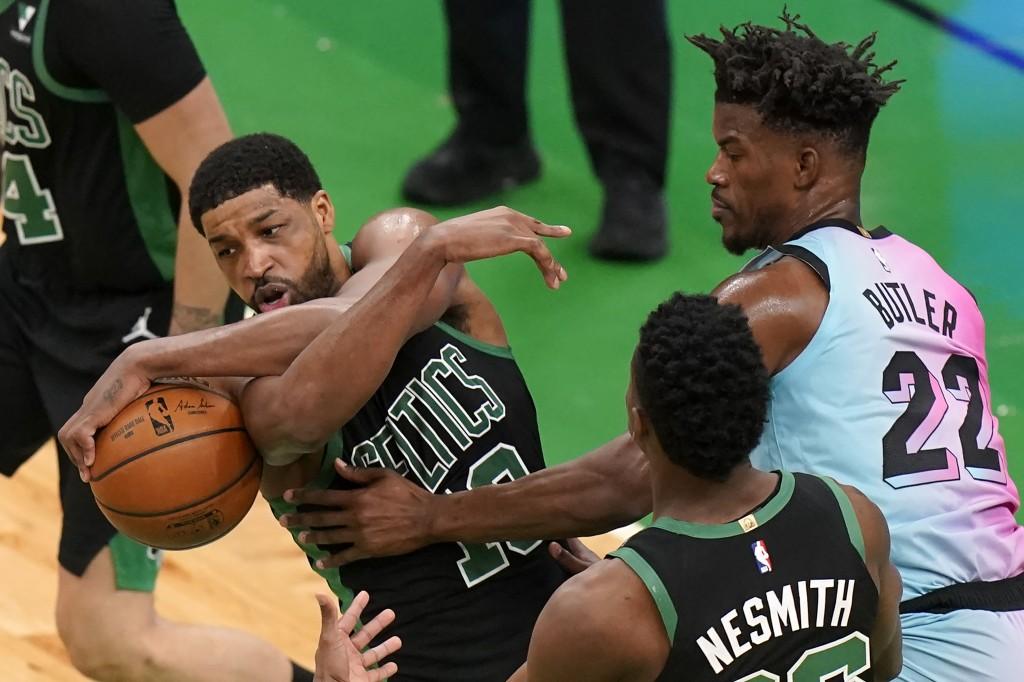 Boston Celtics' Tristan Thompson, left, grips the ball under pressure from Miami Heat's Jimmy Butler, right, as Celtics' Aaron Nesmith, center, looks ...