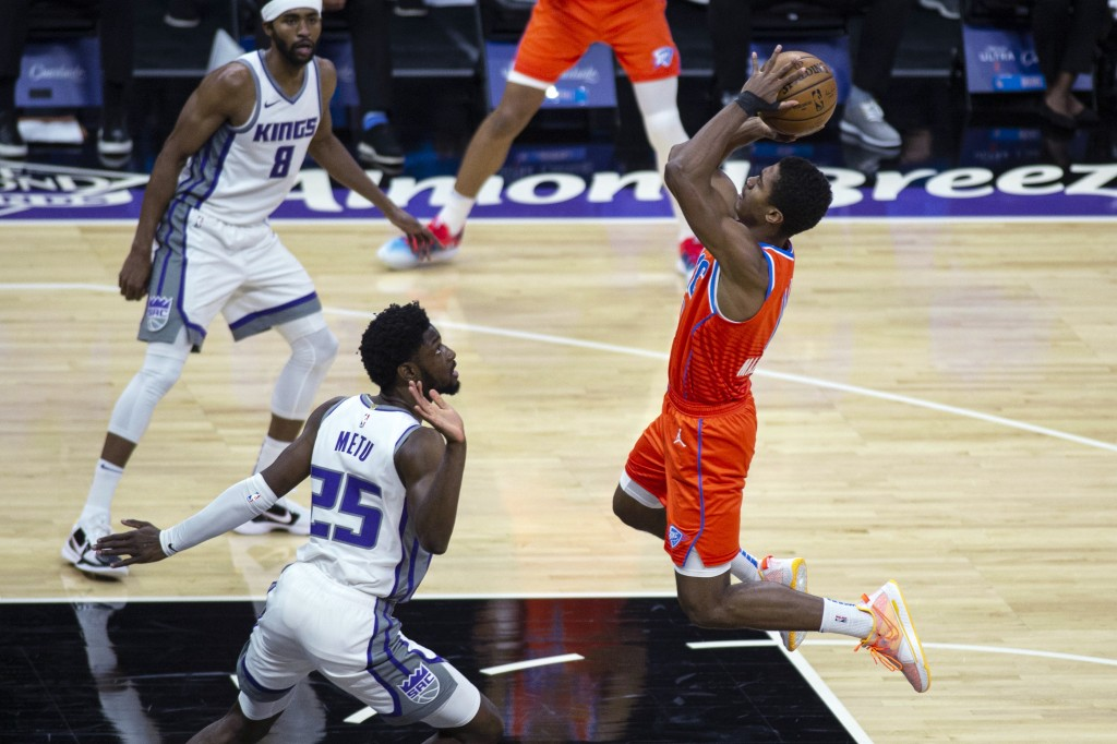 Oklahoma City Thunder guard Theo Maledon (11) drives to the basket as Sacramento Kings forward Chimezie Metu (25) defends during the second quarter of...