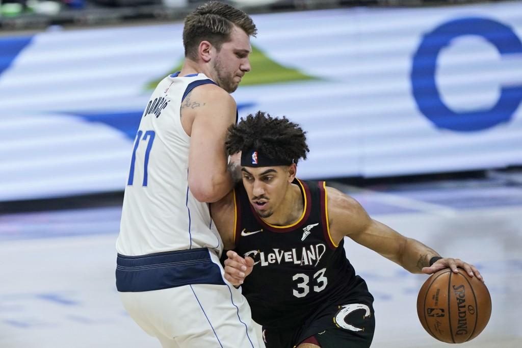 Dallas Mavericks' Willie Cauley-Stein (33) drives against Dallas Mavericks' Luka Doncic (77) during the first half of an NBA basketball game Sunday, M...