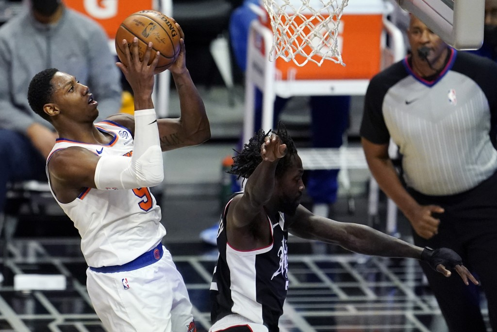 New York Knicks guard RJ Barrett, left, drives past Los Angeles Clippers guard Patrick Beverley during the first half of an NBA basketball game Sunday...