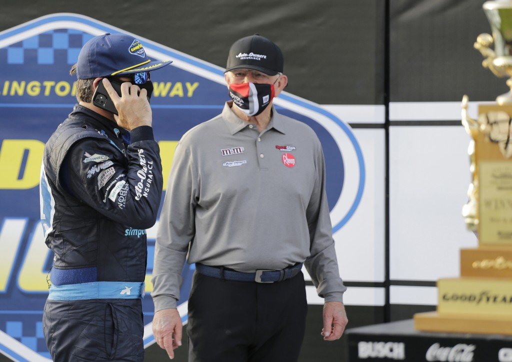Martin Truex Jr. talks on a cell phone as team owner Joe Gibbs stands nearby after Truex won the NASCAR Cup Series auto race at Darlington Raceway, Su...