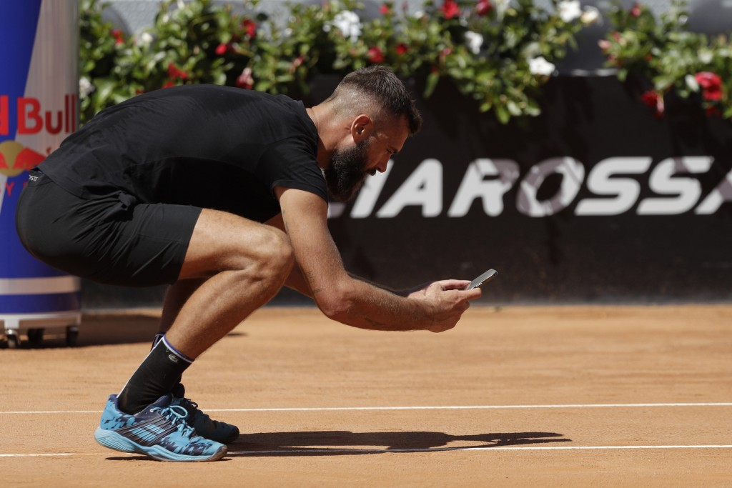 France's Benoit Paire takes a picture with his phone to a sign left by a ball he shot on the line as he argues with the umpire during his match with I...