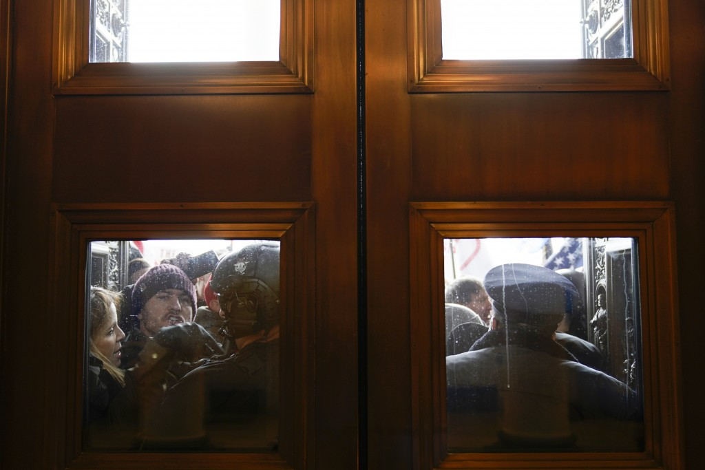 FILE - In this Jan 6, 2021, file photo, U.S. Capitol Police try to hold back rioters outside the east doors to the House side of the U.S. Capitol. At ...