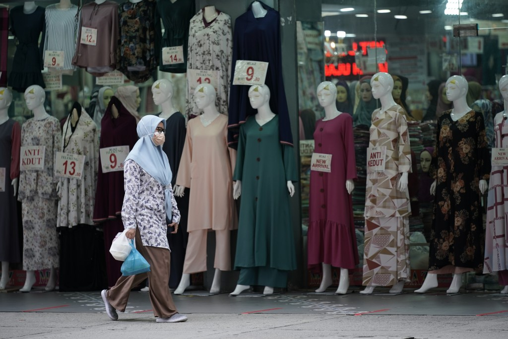 In this Friday, April 19, 2021, photo, a woman wearing a protective mask passes a clothing shop in the Ramadan bazaar in Kuala Lumpur, Malaysia. Malay...