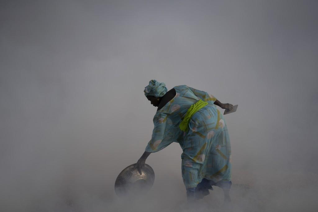Ndeye Yacine Dieng drops embers over peanut shells covering fish as she walks amidst the smoke on Bargny beach, some 35 kilometers (22 miles) east of ...