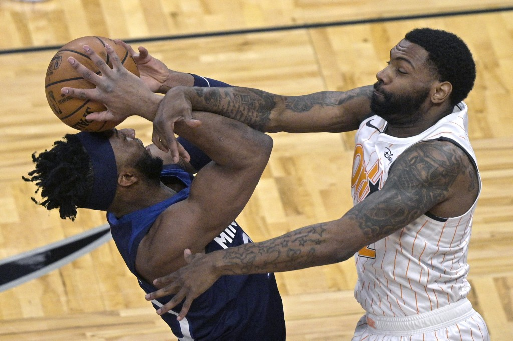 Minnesota Timberwolves forward Josh Okogie, left, is fouled by Orlando Magic guard Sindarius Thornwell while going up to shoot during the first half o...