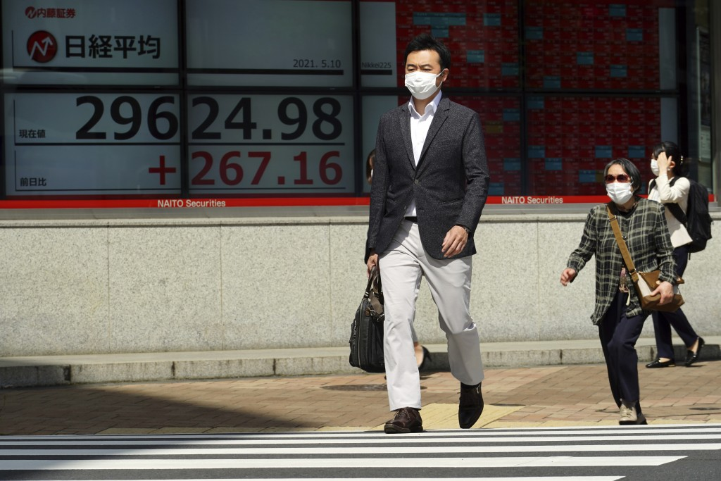People wearing protective masks walk in front of an electronic stock board showing Japan's Nikkei 225 index at a securities firm Monday, May 10, 2021,...