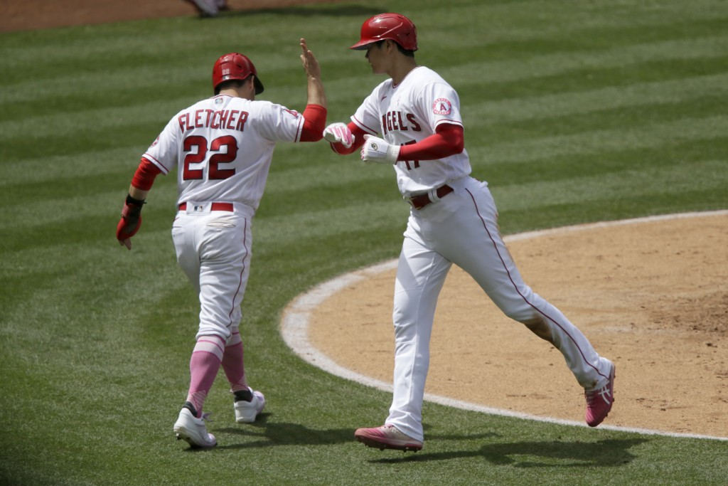 Los Angeles Angels' David Fletcher, left, greets designated hitter Shohei Ohtani after they scores on a ground-rule double by Jared Walsh during the t...