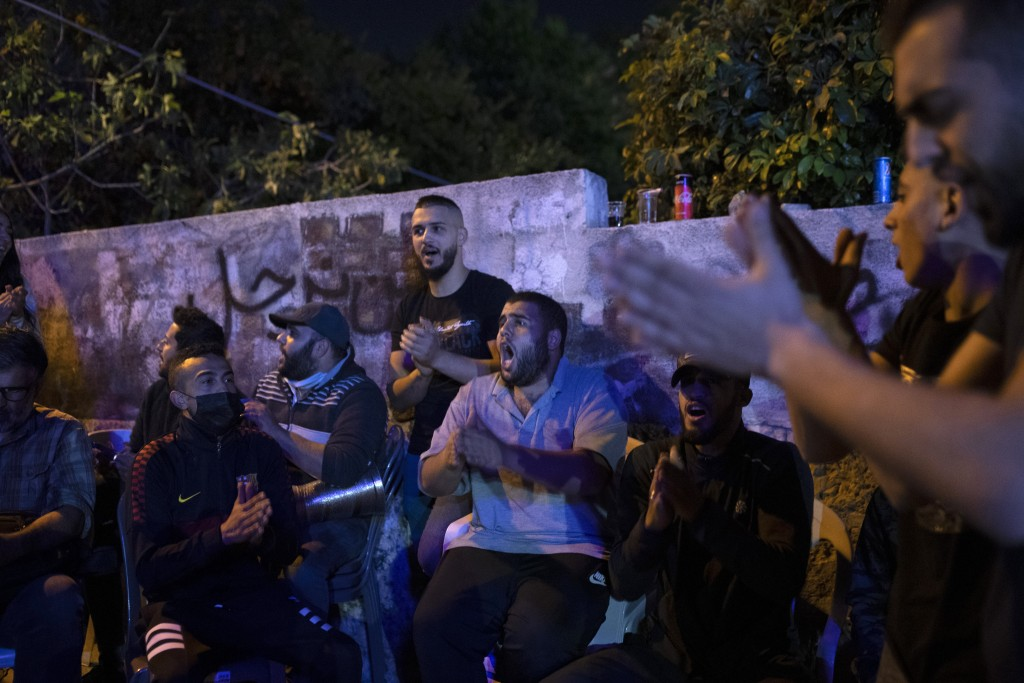 Palestinians sing during an ongoing protest against the forcible eviction of Palestinians from their homes in the Sheikh Jarrah neighborhood of east J...